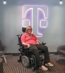 Susan Jolly seated in front of the T-Mobile logo