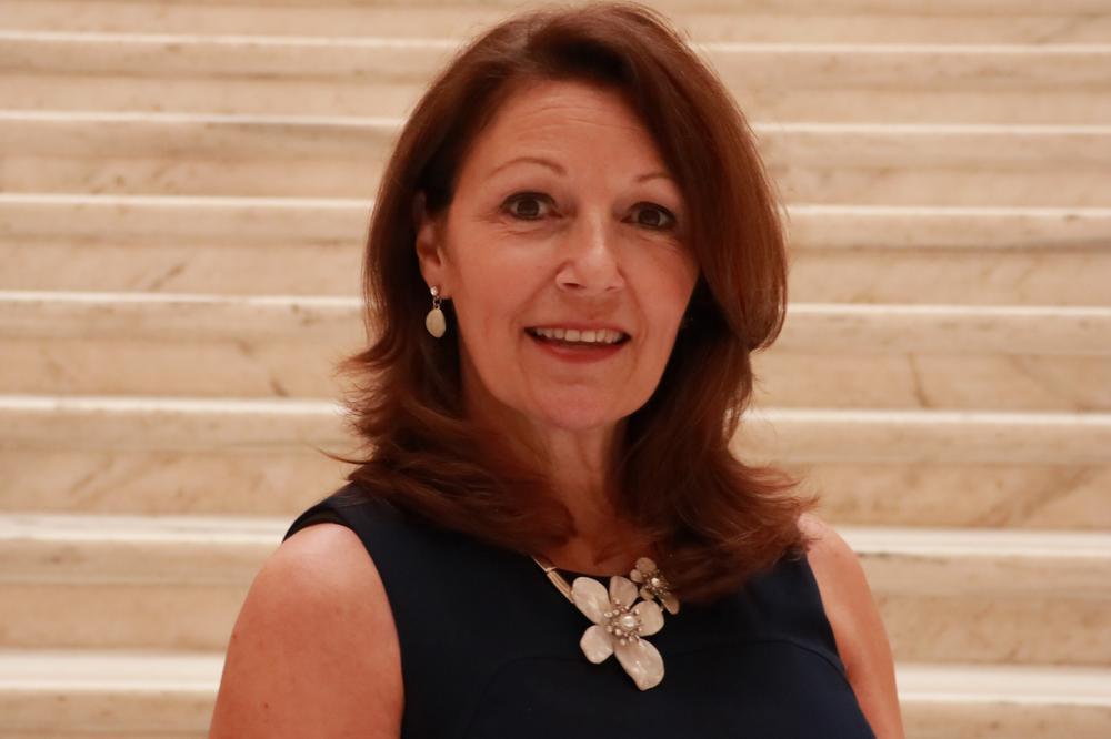 Woman in dark dress smiles at camera