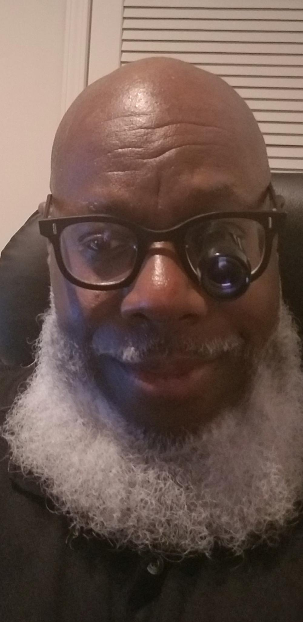 Ken Armstrong wears glasses and has a white beard